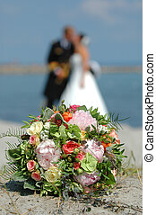bouquet, bride and groom. The focus is only on the bouquet.