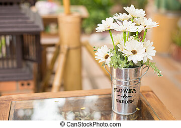 bouquet daisies in zinc cans on table in coffee shop