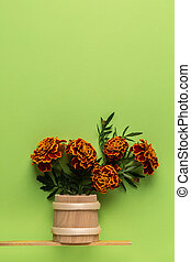 Bouquet flowers marigold in a wooden vase on a green background.