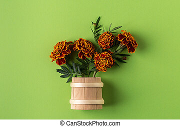 Bouquet flowers marigold in a wooden vase on a green background