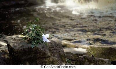 Bouquet flowers near waterfall