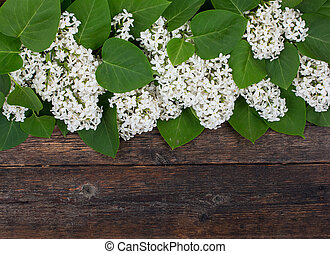 Bouquet, flowers of white lilac lying on the old, rustic boards of dark wood.