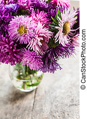 bouquet of asters in a vase on a wooden background