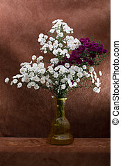 Bouquet of autumn asters in a glass vase on a brown background