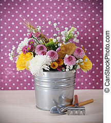 Bouquet of autumn flowers in the iron pot with garden tools