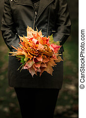 bouquet of autumn leaves in the woman hands