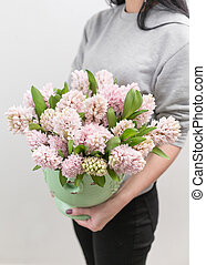Bouquet of Beautiful pink hyacinths. Spring flowers in vase in woman hand. bulbous plant. Vertical photo