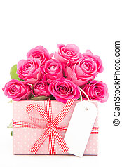 Bouquet of beautiful pink roses next to a pink gift with a blank card on white background close up