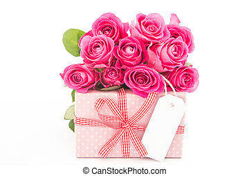 Bouquet of beautiful pink roses next to a pink gift with an empty card on white background close up