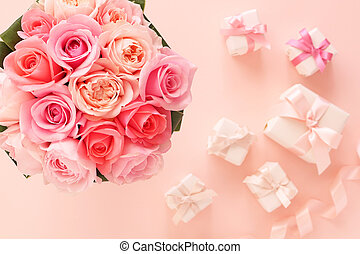 Bouquet of beautiful pink roses with gifts on pastel pink background , top view