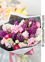 Bouquet of Beautiful violet and pink hyacinths. Spring flowers in vase on gray table background. bulbous plant