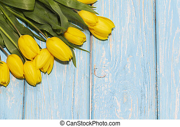 bouquet of beautiful yellow tulips on a light blue background.