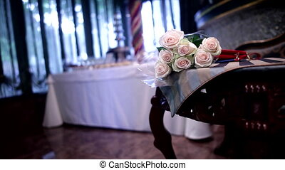 Bouquet of beige roses on brown wooden table in restaurant.