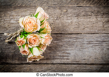 Bouquet of beige roses on wooden background
