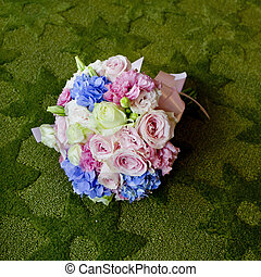 Bouquet of blooming colorful flowers on a green carpet backgroun