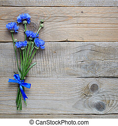 Bouquet of blue cornflowers on old wooden background