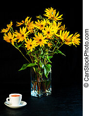Bouquet of bright fresh yellow flowers and white cup of coffee on black background. Jerusalem artichoke flowers in glass transparent vase. Low key. Vertical orientation.