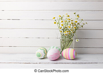 Bouquet of chamomiles in a glass vase and easter eggs in pastel color on white vintage planks