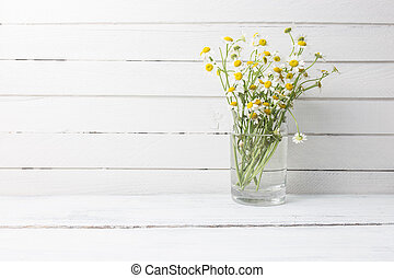 Bouquet of chamomiles in a glass vase on wooden background