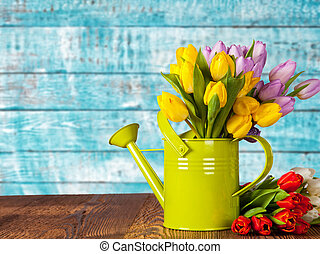 Bouquet of colored tulips with watering can