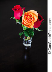 bouquet of colorful roses in a vase on a wooden table