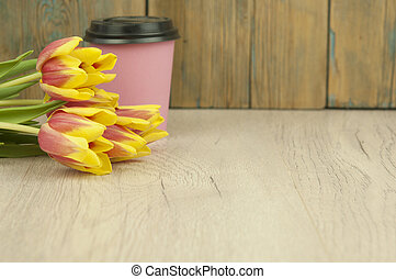 Bouquet of colorful tulips with paper coffee cup on a white wooden background with copy space for your text