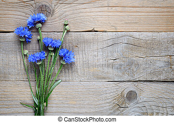 Bouquet of cornflowers on wooden background