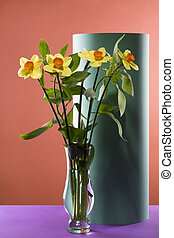 Bouquet of daffodils in a glass vase on a colored background