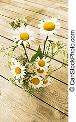 Bouquet of daisies. Chamomile flowers stand in a vase on a wooden background. View from above.