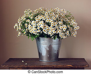 bouquet of daisies in a bucket on the table.