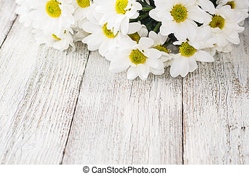 bouquet of daisies on a white wooden background