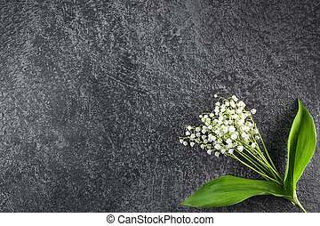 Bouquet of delicate lilies of the valley on a dark background.