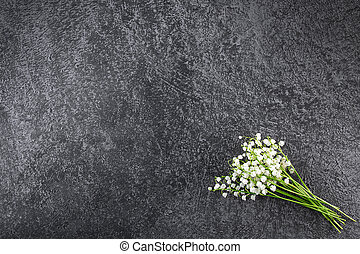 Bouquet of delicate lilies of the valley on a dark background