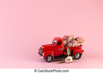 Bouquet of dried roses in the back of a toy truck.