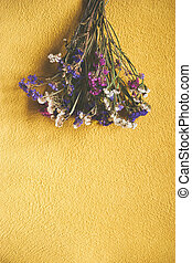 Bouquet of dry flowers on yellow backgrounds