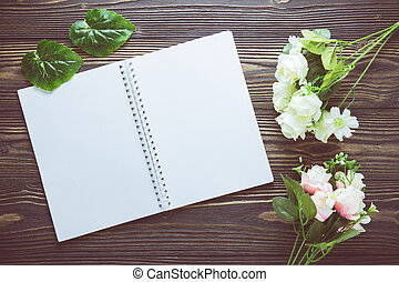 Bouquet of flower and empty diary notebook on rustic wooden table with copy space, mockup template with flower and note, top view, vintage retro style.