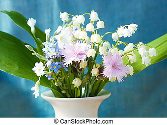 bouquet of flower in vase. Blue clothing background