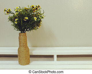 bouquet of flower in vase on wooden background