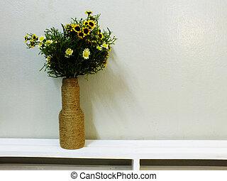 bouquet of flower in vase on wooden blackground