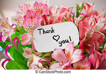 bouquet of flowers and card with lettering thank you