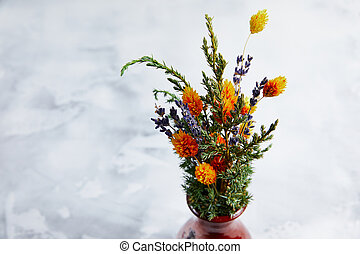 bouquet of flowers in a clay vase on a white marble background