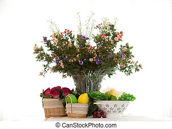 Bouquet of flowers in a decorative vase with fruit