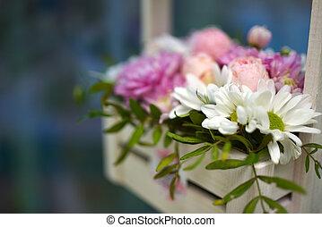 Bouquet of flowers in a wooden basket on the window