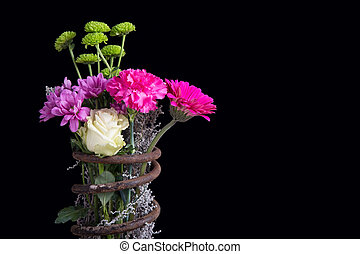 Bouquet of flowers in metal spring isolated on black background