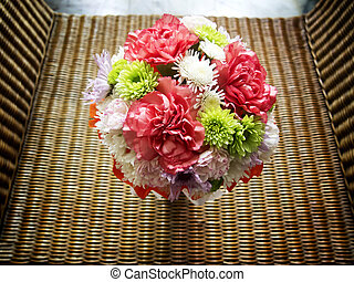 Bouquet of flowers on basketwork chair