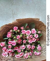 Bouquet of flowers. Pink little bush roses lying on the table