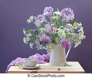 Still life with garden and wild flowers in a jug and a tea pair on a table
