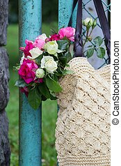 bouquet of fragrant English pink and white roses in a bag of raffia hanging on the fence