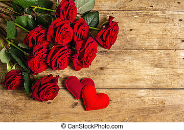 Bouquet of fresh burgundy roses and soft felt hearts on a vintage wooden background