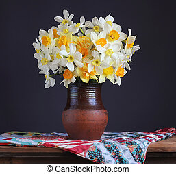 Bouquet of fresh garden daffodils in a clay jug on the table.